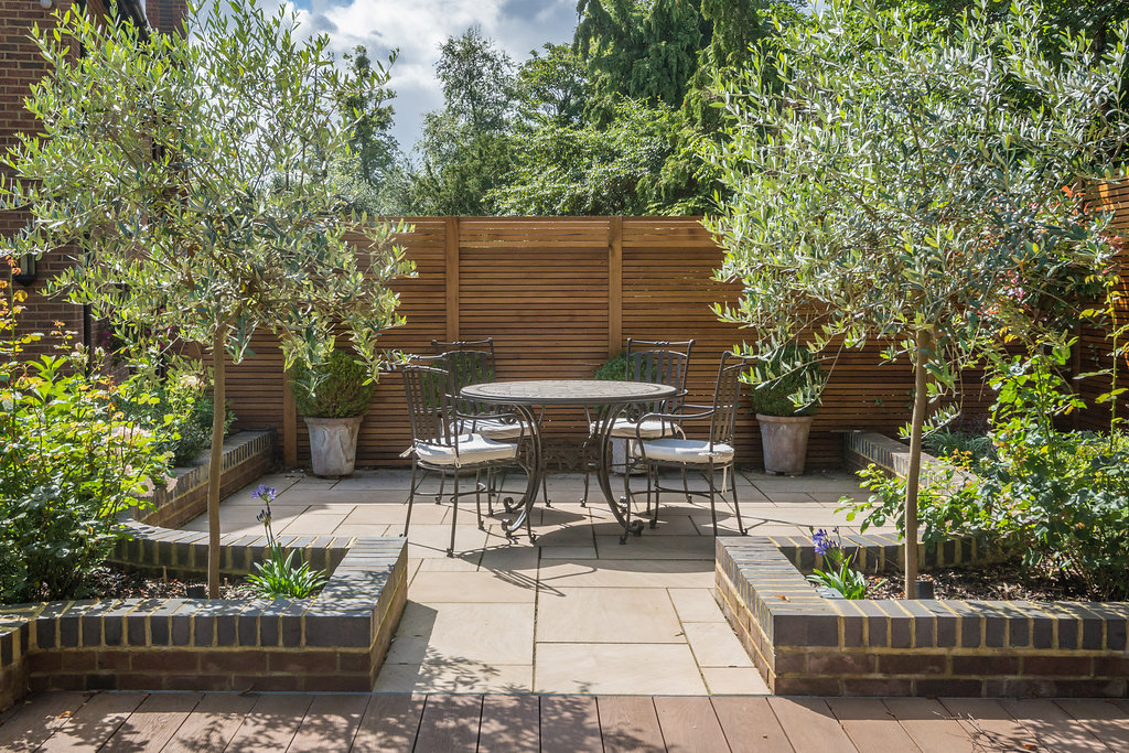outdoor table and chairs in landscaped residential garden