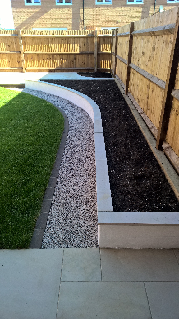 landscaped contemporary garden with smooth sandstone paving, raised beds and patio section