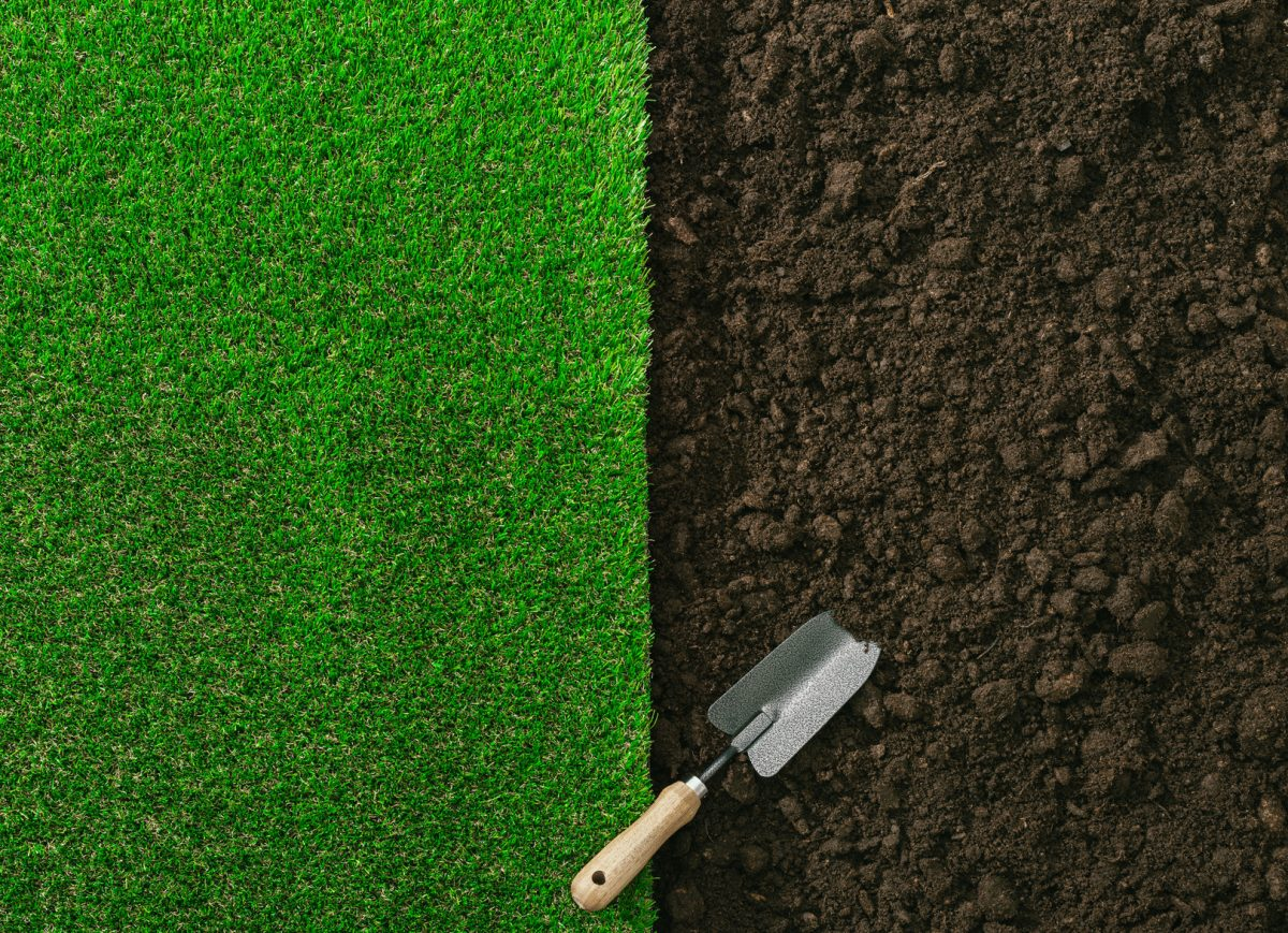 Gardening trowel on fertile soil and grass,