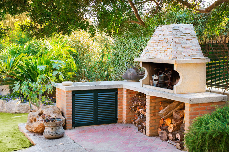 External Wood oven with burning fire and firewood